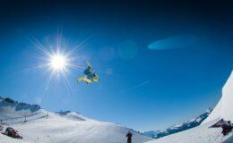 Mand der tager et hop på snowboard